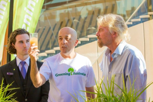Jonathan Duddles of Greening Australia shows Sir Richard Branson a soil ...
